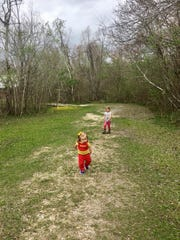 Avery and Marie Guidry follow their parents down a trail at St. Bernard State Park.