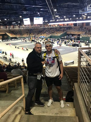Lely wrestler Marlon Moreta, right, celebrates his sixth-place finish in the Class 1A 170-pound state bracket, with his father Marco on Saturday in Kissimmee.