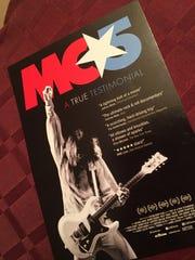 "A placard celebrating ""MC5: A True Testimonial"" was"