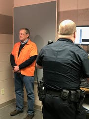 Tom Angst has his mug shot taken at the Manitowoc Police