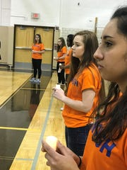 Members of Students Demand Action hold candles in honor