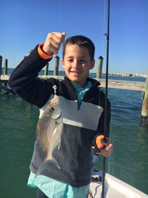 Brody Flynn, Capt. Charlie Conner's grandson, with a big sand perch he caught while fishing during spring break.