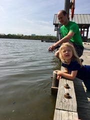 Eric Guidry and daughter Avery, 3, fish and look for hermit crabs from a crabbing pier at Grand Isle State Park.