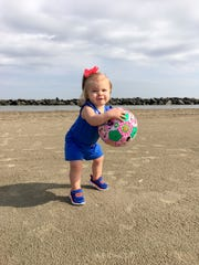 Marie Guidry, 1, plays with a soccer ball on the beach