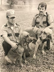 Johnny Newberry rests at left with Little Red, while head dog trainer Sammy Joe Chapman admires Sandy. The two bloodhounds tracked down most of the fugitives in the June 1977 breakout from Brushy Mountain State Prison, including James Earl Ray.