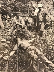Sammy Chapman, right, the dog handler who tracked down James Earl Ray, shows how he found him on June 13, 1977. Playing the part of Ray is prison guard Rick Trail. Trail is lying in the exact spot Ray was found. Others pictured from left are Bill Garrison, John Heidle, Johnny Newberry and Chapman.