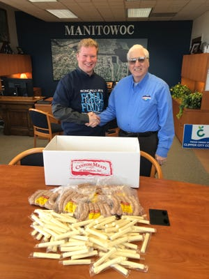 Manitowoc Mayor Justin Nickels (left) shakes hands with Marathon City Village President John Small. Small delivered 10 pounds of cheese and 10 pounds of brats from Custom Meats of Marathon Inc. to the Manitowoc mayor as part of a friendly wager over the WIAA boys basketball championship game between Manitowoc Roncalli and Marathon.