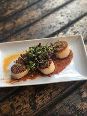 Scallops with Romesco are a specialty dish at Movida.