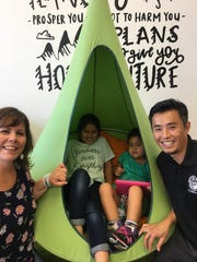 Heather and Vincent Nghi flank two of their four children: Katelyn, 8, and Lilly, 4. Lilly will join the Champions Club, a ministry for children with special needs, at its grand opening Easter Sunday.