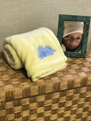 A blanket sits next to a framed photograph of Carson