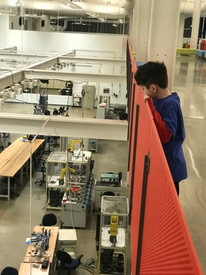 A Northfield Elementary student peeks over a barrier to get a look at a lab at the Tennessee Center for Applied Technology in Smyrna during a schoolwide family night held April 5.