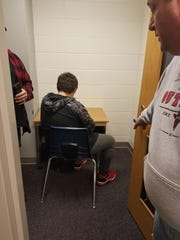 Matthew Schoenecker sits in an isolated cubicle as a consequence of wearing his gun T-shirt to school without permission of the principal.