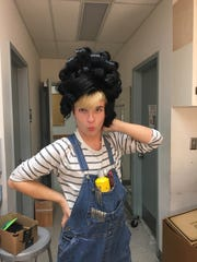 """Jake Thereault, a Salisbury University student, playfully poses with a wig to be used in """"Hairspray."""" Thereault styles the wigs."""