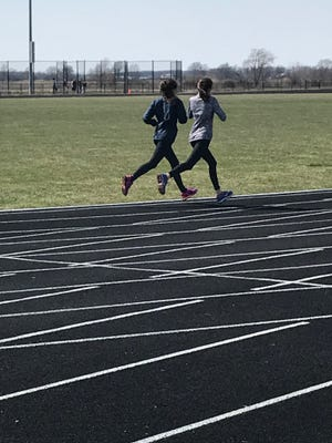 A pair of River Valley girls track team members work out during a rare warm day on Thursday. The Vikings finished second at the Bellefontaine Relays on Friday.