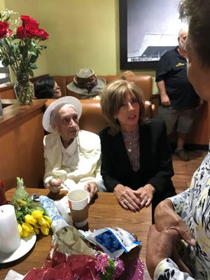 Gifts of flowers surrounded Sister Marie Alice at her 100th birthday party at the Port St. Lucie Denny's.