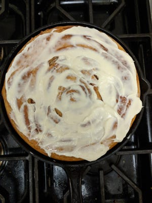 The roll is baked in a 9-inch cast iron skillet, filled with swirls of cinnamon and brown sugar, and covered in cream-cheese frosting.