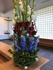 An arrangement of red, white and blue flowers following