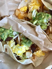 A pair of breakfast tacos, one with chorizo the other