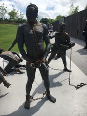 A sculpture of a black man in chains at the EJI Memorial.