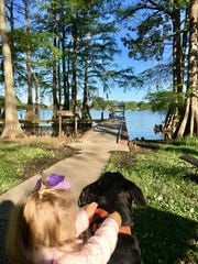 Marie Guidry, 1, holds on to her dog Molly Sue while her big sister Avery fishes with dad Eric Guidry on Lake Bruin.