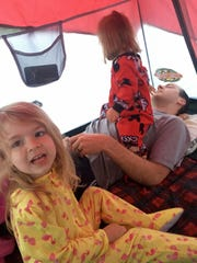 Avery and Marie Guidry play on their dad in the tent