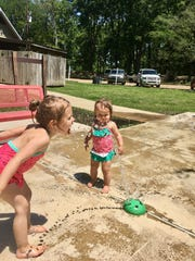 Sisters Avery and Marie Guidry play at the splash pad at Lake Bruin State Park in St. Joseph.