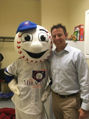 Brook Whiffen, right, president of the board of directors for the Miracle League of Santa Rosa, poses with Homer, the league mascot, on Wednesday, May 2, 2018 in Gulf Breeze.