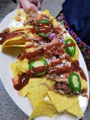 A server serves up a platter of pulled pork nachos