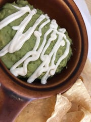 Guacamole drizzled with crema and served with homemade