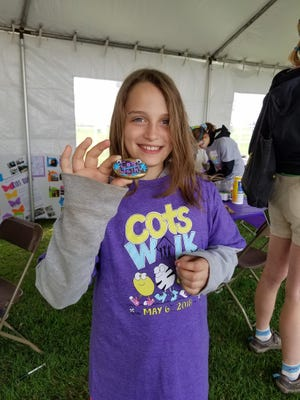 Alaina Cheeseman, 9, of Colchester shares her gratitude stone she painted before the 29th Annual COTS Walk.