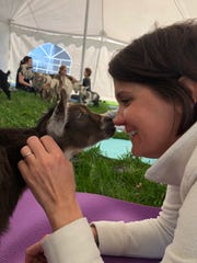 Nancy Hakes of North Liberty accepts a nose nuzzle from one of the dozen baby goats that joined the special yoga class at Lucky Star Farm in late April.