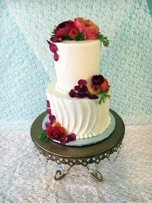 For decorations, bakery owner Jennifer Goldbeck kept it simple, with vanilla buttercream in smooth and textured finishes and fresh flowers.