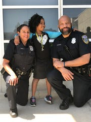 Rosalyn Baldwin, 8, poses with two Milwaukee police officers. The Louisiana girl is on a mission to give hugs to officers in all 50 states.