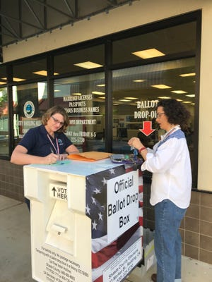 Staff at the Shasta County Clerk's office collect mail-in/drop-off ballots in front of the office's location on the Redding Promenade.