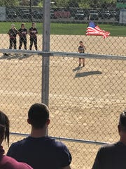 Members of the SPASH softball team stand at attention in the circle for the national anthem as Braxton Lake holds the flag before Friday's game.