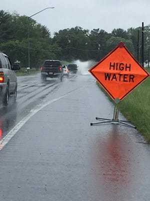 A car traveling on westbound Nanticoke Road throws up a wake just ahead of a sign warning of high water in 2017.