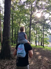Eric Guidry carries daughter Avery, 3, on his shoulders as they walk down a trail along the water at Chemin-A-Haut State Park in Bastrop.
