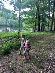 Sisters Avery and Marie Guidry walk down a trail along