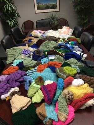 These hats and scarves all came in too late to distribute this winter. Community Hope, an organization that serves veterans is going to take them all and distribute them to veterans and their families this fall.