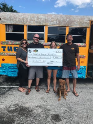 Tiffany and Chris Ellison of Shorepound productions and Jordan, Tara and Nugget Schwartz of Ohana Surf Shop present the check.