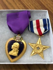 A Purple Heart medal and Silver Star medal awarded