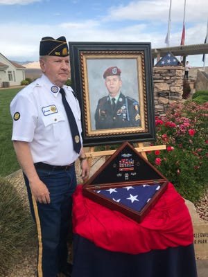 Jerome Gourley, a retired lieutenant colonel with the U.S. Army Corps of Engineers, poses Monday with a portrait of his son, Gregson Gourley, who was killed in action in Iraq in 2006 while serving with the  101st Airborne Division.