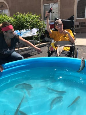 Bella Terra resident Greg Sybrant catches a fish as employee Rokell Bohman cheers at the Cedar City nursing home on May 31, 2018.