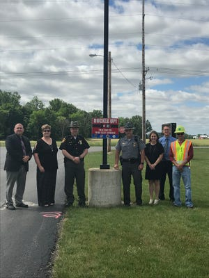 """A new """"Buckle Up"""" sign was posted at the exit of the Colonel Crawford K-12 Building. From left, are Colonel Crawford High School principal Jake Bruner, elementary principal Cindy Voss, Sheriff Scott Kent, Lieutenant Scott Rike, intermediate principal April Bond, superintendent Todd Martin, and Mike Stansberry of ODOT."""