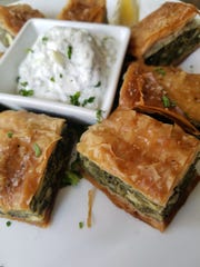 The spanakopita at the Famous Bistro is filled with tangy spinach, herbs and feta cheese. It is served with the house thick and fluffy tzatziki sauce.