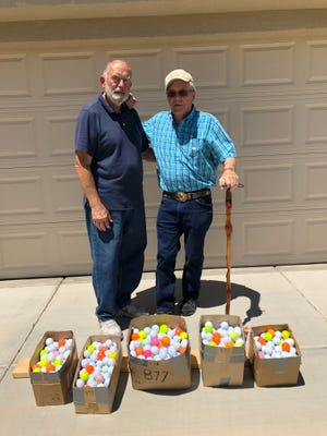 Mesquite residents Karl Gustavesson and Robert Olson stand in front of golf balls they helped donate to the Virgin Valley Junior Golf Association on June 12, 2018.