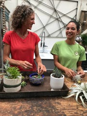 Mimi Martinson, left, who with her husband, Allen, owns Martinson's Garden Works in Ridgeland, and Kristen Lewis, an employee at Martinson's, place plants in pots for the newly opened sunroom at the garden center.