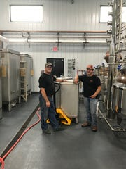 Employees Don Daun, left, and Bryce Retzer work in the distillery.