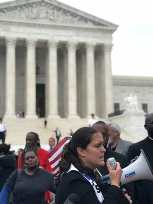The Rev. Liz Theoharis, co-chair of the Poor People's Campaign, leads a prayer vigil outside the U.S. Supreme Court before being arrested June 11.