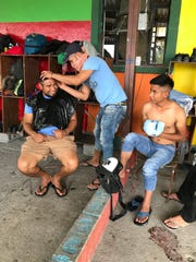 Central American migrants give each other haircuts